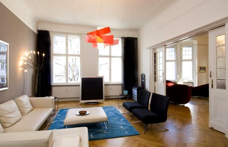 studio apartment design ideas blue carpet black sofas red lantern chandelier palm standing lamp 1